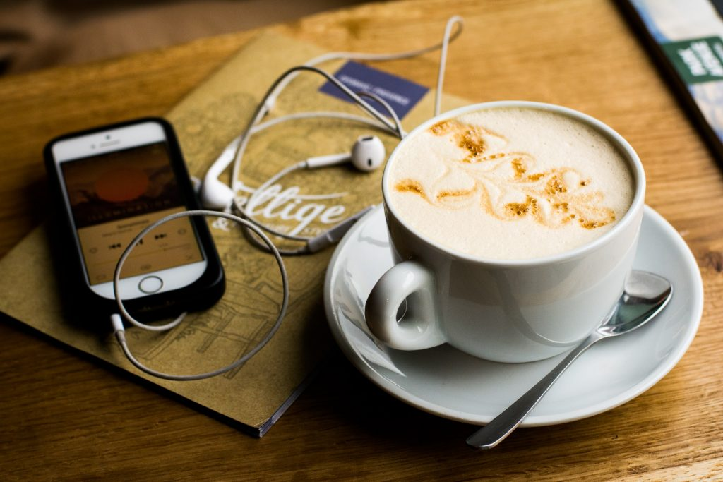 Coffee, iphone headphones listen to podcast in east london